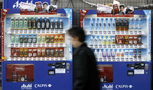 Man walks past vending machines of Asahi Soft Drinks in Tokyo.