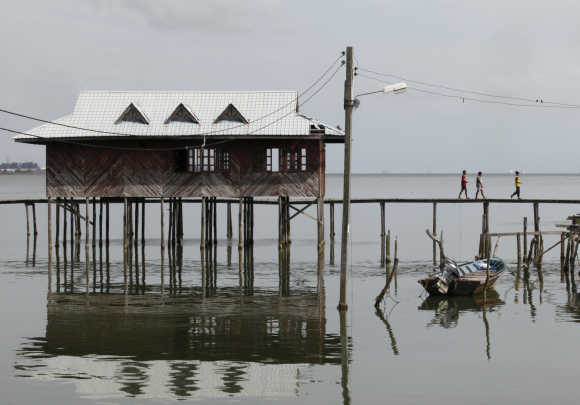 Residents walk on a wooden walkway at a water village on Malaysia's island of Labuan.