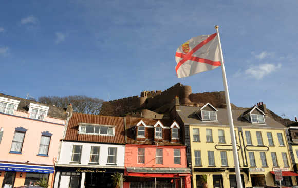 The Mont Orgueil Castle is seen behind an island flag at Gorey Harbour in Jersey.