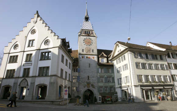 People walk past the 52 metre high Clock Tower, the landmark of the historical part the town of Zug, about 35km south of Zurich.