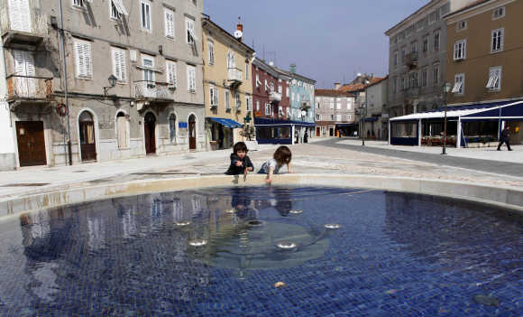 Children play near a public fountain in Rijeka on the northern Adriatic island of Cres, Croatia.