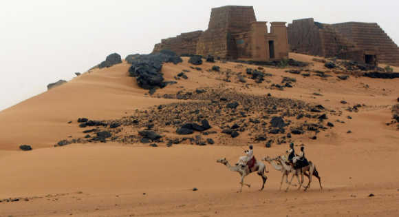 Men ride camels near the site of 44 Nubian pyramids of kings and queens in the ruins of the ancient city of Meroe next to Begrawiya, in Sudan.