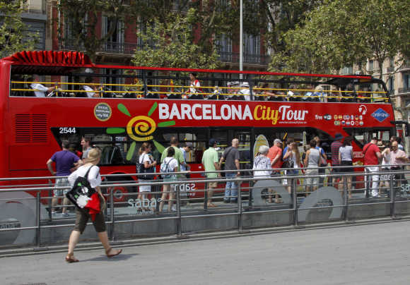 Tourists line up to board the Barcelona city tour bus at Plaza Catalunya in central Barcelona.