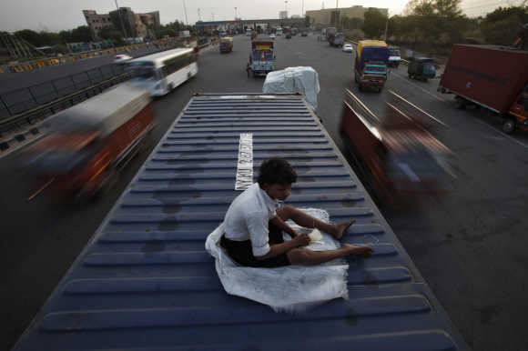 Helper of a driver rests on top of his parked truck along a busy highway on the outskirts of New Delhi.