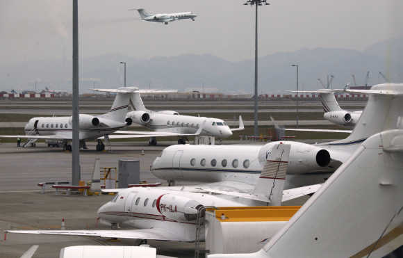 A business jet takes off as others are parked at the Hong Kong Airport.