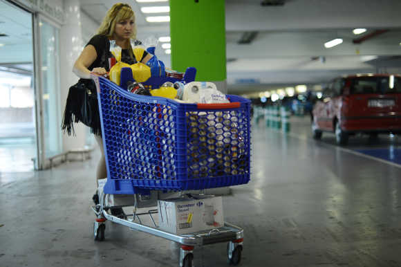 A woman pushes a shopping trolley in the car park of a supermarket near Bilbao.