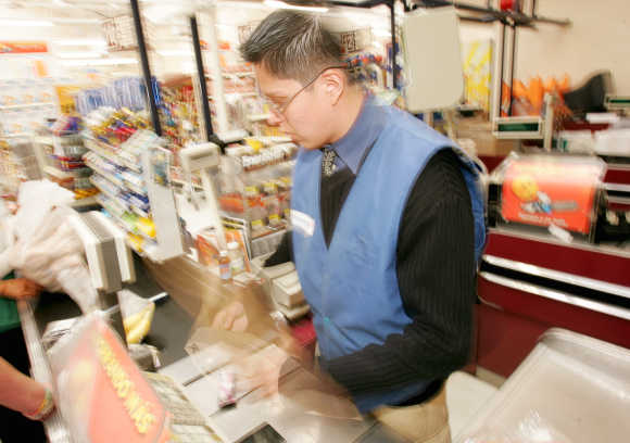 A cashier is a blur of activity as he speeds products past the electric point of sale bar code sensor in Mexico City.