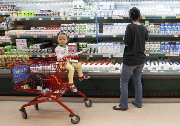 A customer looks at milk as a girl sits on a shopping cart at a supermarket in Seoul.