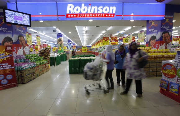 People shop at a Robinson supermarket outlet in Cileduk of South Jakarta.
