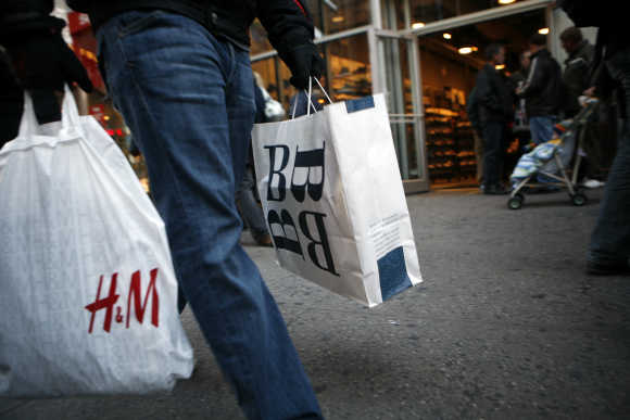 A shopper carrying shopping bags walks past retail stores in New York's Times Square.