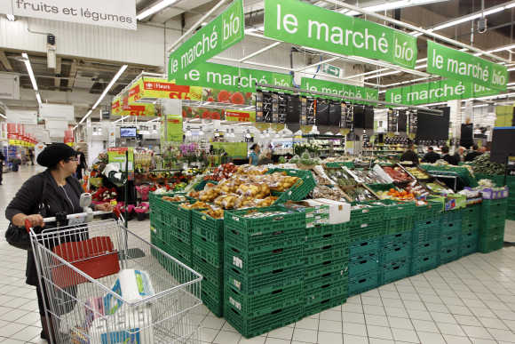 A shopper pushes a shopping trolley down an aisle at a supermarket in Charenton near Paris.