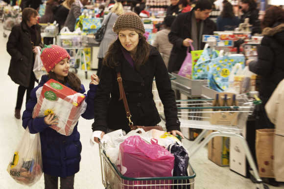 Shoppers move through the cashier area at a Morrisons supermarket ahead of Christmas weekend in London.