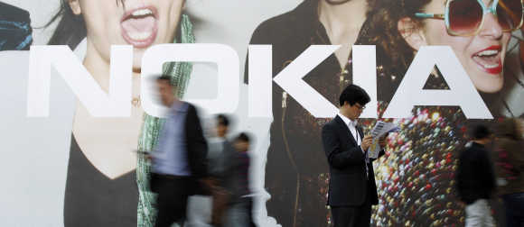 Visitors walk past a Nokia board as a man checks a map during the Mobile World Congress in Barcelona.