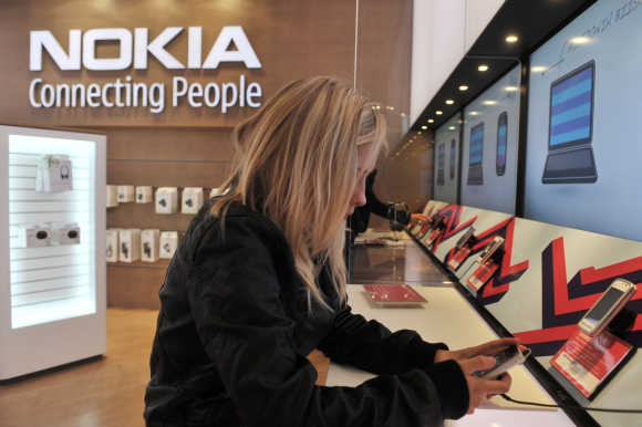A girl tests out the new Nokia N8 mobile phone at the Nokia Flagship store in Helsinki.