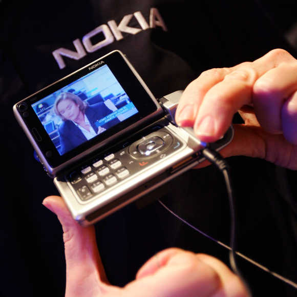 A visitor holds Nokia N92 mobile TV with a 2.8 inch screen during Nokia conference in Barcelona.