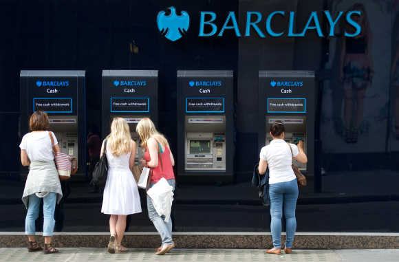 People use a line of Barclays cash dispensers in central London.