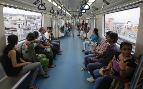 Commuters ride inside a carriage of a Namma Metro train as it travels along an elevated track in the Indira Nagar area of Bengaluru.