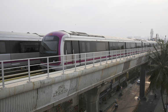 A Namma Metro train travels along an elevated track in the Indira Nagar area of Bangalore.