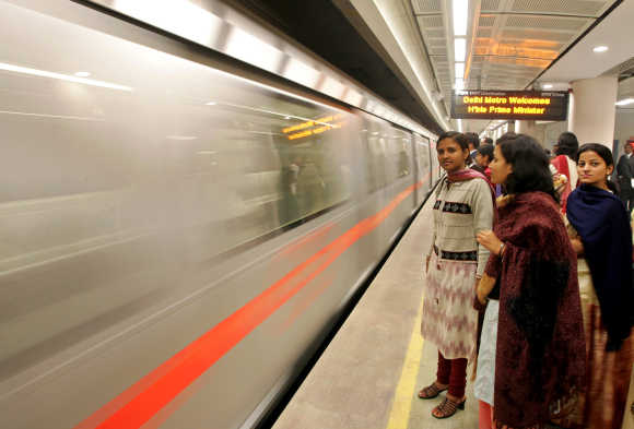 Passengers wait to board Metro train in New Delhi.
