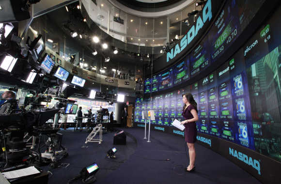 A television reporter broadcasts from the Nasdaq Marketsite in New York