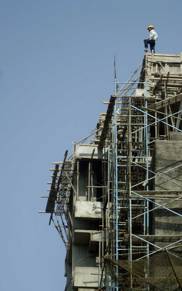A worker stands on top of a building under construction in Mumbai.