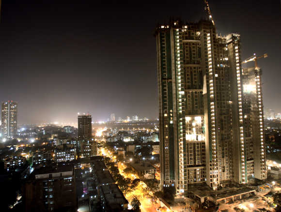 A high-rise building is lit up during construction in Mumbai.