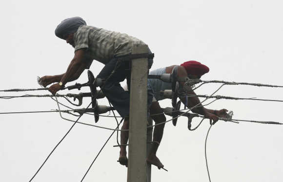 Workers repair high voltage power lines at Fatehpur Sylwa in Punjab.