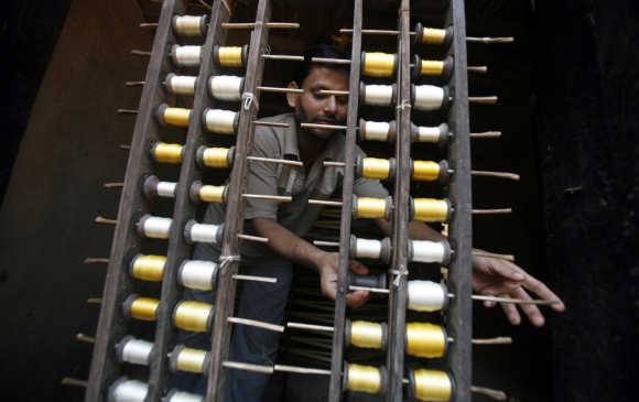 A weaver changes a spool of silk yarn for making fabrics in Margram village, about 240km north of Kolkata.