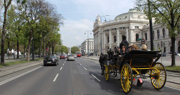 A traditional Fiaker horse carriage passes Burgtheater theatre in Vienna.