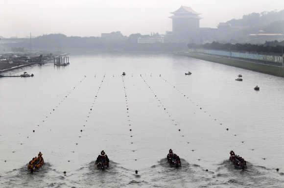 Participants compete in a dragon boat race to mark the upcoming Dragon Boat Festival in Keelung River in Taipei.