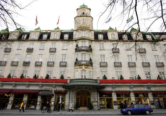 People walk past the Grand Hotel in Oslo.