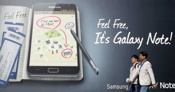 Visitors walk past a Samsung Galaxy tablet advertisement during the Mobile World Congress in Barcelona.