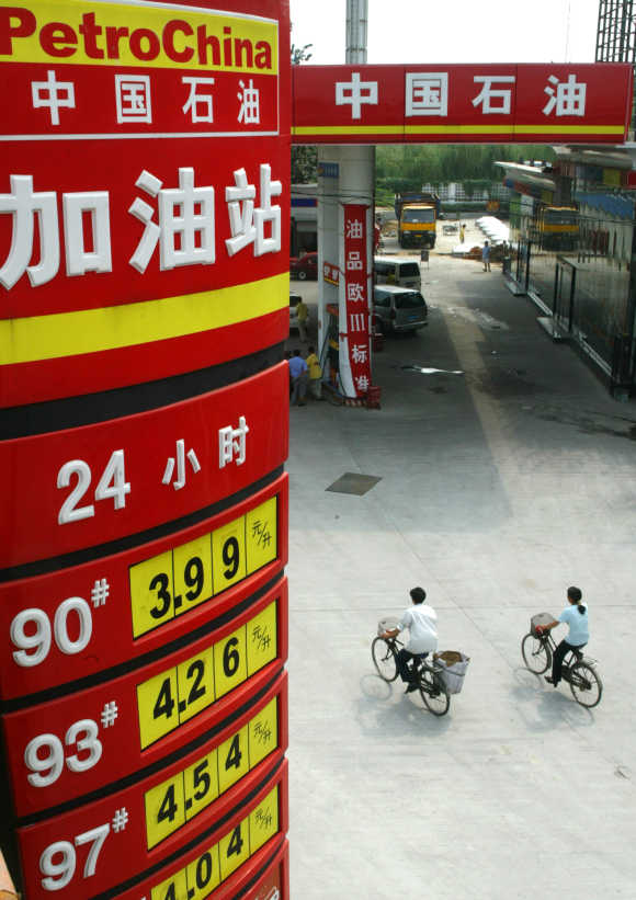 Cyclists pass under board displaying oil prices at PetroChina station in Beijing.