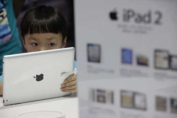 A boy views an iPad 2 tablet computer at an Apple dealership in Wuhan, Hubei province.