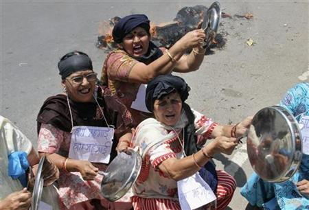 Demonstrators bang kitchen utensils and shout slogans during a protest against the price hike in petrol
