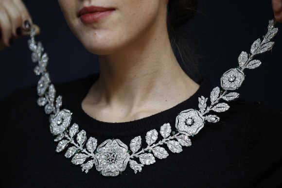 A employee holds a Belle Epoque diamond and emerald neckace during an auction preview at Christie's in London.