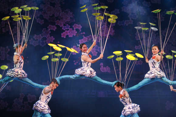 Artistes display their plate-spinning skills during an acrobatics show in Beijing.
