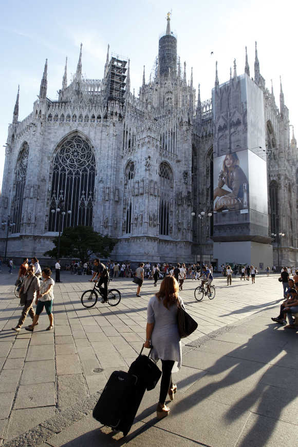 An advertisement is seen on Duomo cathedral as people walk across Duomo square in Milan.