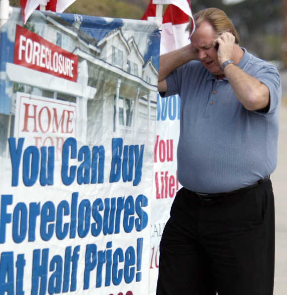 Home Center Realty owner Ron Barnard talks on his mobile phone as he stands next to a sign advertising his business in Norco, California.