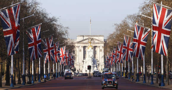 A London taxi makes its way down the Mall, decked out in Union flags and with Buckingham Palace in the background.