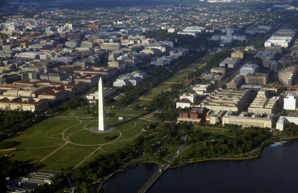 Downtown Washington is seen in an aerial view. At bottom left is the World War II memorial with the Washington Monument and National Mall at centre and the US Capitol building at upper right.