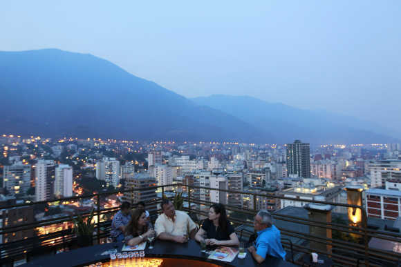 People have a drink at 360, a three-tiered rooftop bar, in capital Caracas.