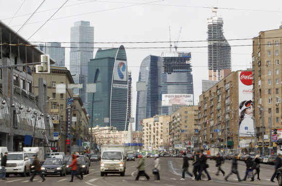 People cross a road, with the Vostok or East tower, part of the Federation complex in the 'Moscow City' business district, seen in the background in Moscow.