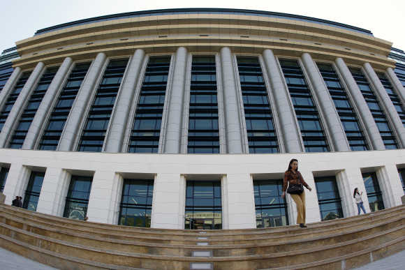A woman walks down the steps in front of Romania's National Library in Bucharest.