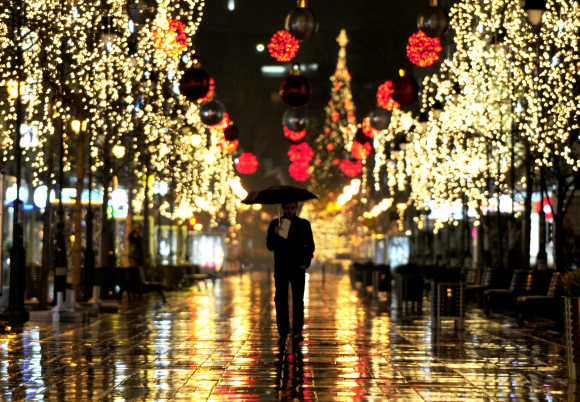 A man walks near trees illuminated with Christmas lights in the Macedonian capital of Skopje.