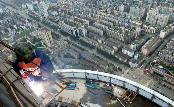 A welder works outside a building in downtown Chengdu.