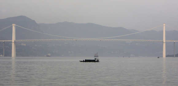 A man steers his small boat past a bridge on the Yangtze River near the city of Wanzhou in the Chongqing municipality in the south-west part of China.