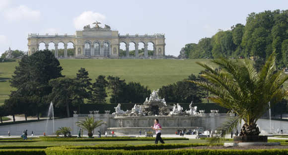 A jogger crosses the garden of Schoenbrunn castle in front of Gloriette in Vienna.
