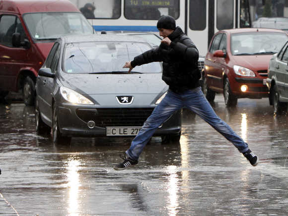 A man crosses the street in the rain in Chisinau, Moldova.