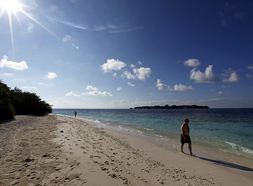 Tourists enjoy the beach at a resort island at the Male Atoll.